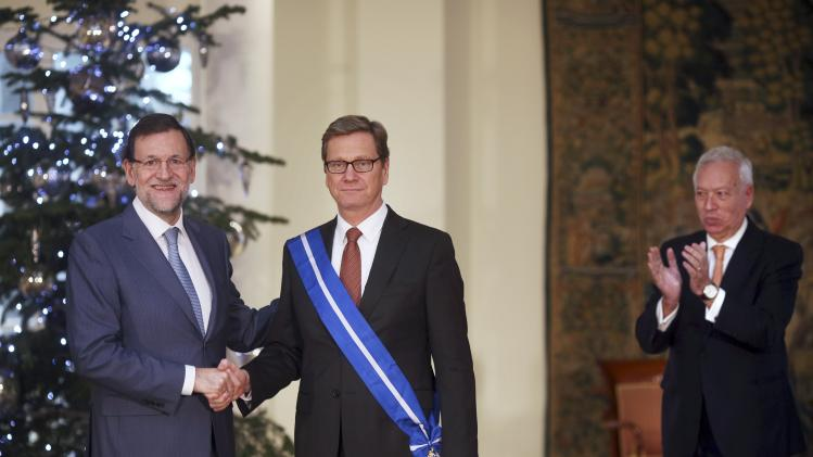 Spanish PM Rajoy and German Foreign Minister Westerwelle pose after Rajoy decorated Westerwelle with the Grand Cross of the Order of Civil Merit at Madrid's Moncloa Palace