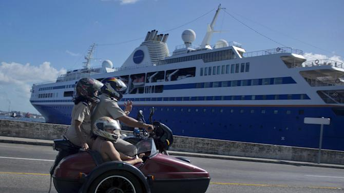 """FILE - In this Dec. 9, 2013 file photo, a trio of people on a motorcycle and sidecar drive past the """"Semester at Sea"""" cruise ship docked in Havana's harbor, Cuba. President Barack Obama's announcement Wednesday, Dec. 17, 2014, of plans to re-establish diplomatic ties with the Caribbean nation gives hope to airlines, hotel chains and cruise companies _ all which have been quietly eyeing a removal of the travel ban _ that they soon will be able to bring tourists to Cuba. (AP Photo/Ramon Espinosa, File)"""