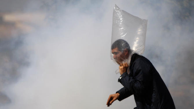 A Palestinian demonstrator protects himself from tear gas during a protest against Israel's separation barrier in the West Bank village of Bilin, near Ramallah, Friday, April. 13, 2012. (AP Photo/Majdi Mohammed)