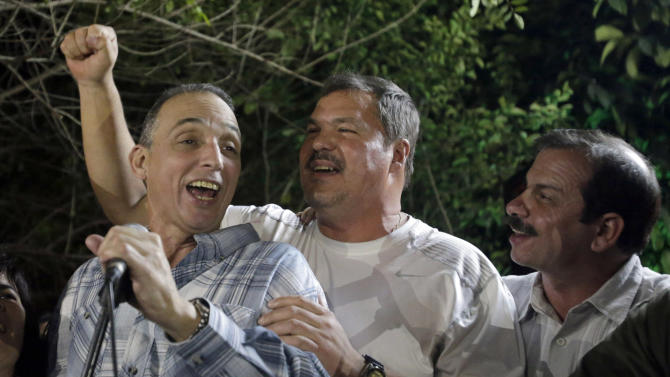 """Antonio Guerrero, left, and Ramon Labanino, two of the three Cubans released under a prisoners swap agreement with the U.S. on Wednesday, sing with Fernando Gonzalez, a fellow member of """"The Cuban Five"""" who had been previously released, during a private celebration in Havana, Cuba, late Friday Dec. 19, 2014.  Guerrero, Labanino and a third man Gerardo Hernandez flew back to their homeland in a quiet exchange of imprisoned spies, including the celebratory release of American Alan Gross, a government contract worker who had been held in Cuba for five years. (AP Photo/Ismael Francisco, Cubadebate)"""
