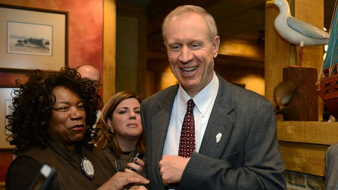 Gov. Bruce Rauner cracks a smile after buying two raffle tickets from Mundelein Vernon Hills Rotary Club member Melvina Lube of Mettawa Monday, March 2, 2015. Gov. Rauner spoke during the group's weekly meeting in Mundelein, Ill. (AP Photo/Daily Herald, Paul Valade) MANDATORY CREDIT, MAGS OUT