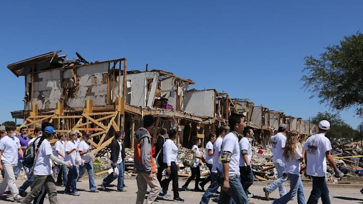 Texas A&M students walk past an apartment complex in West, Texas, Saturday, May 4, 2013, that was damaged due to the explosion at a fertilizer plant on April 17. The plant that exploded, killing 14 people, injuring more than 200 others and causing tens of millions of dollars in damage to the surrounding area, had only $1 million in liability coverage, lawyers said Saturday. (AP Photo/Waco Tribune Herald, Rod Aydelotte)
