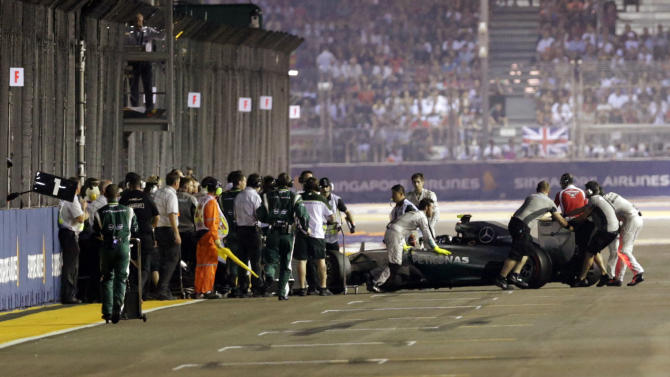 Mercedes Formula One's team pushes the car of Nico Rosberg of Germany out of the pit before the start of the Singapore F1 Grand Prix at the Marina Bay street circuit in Singapore