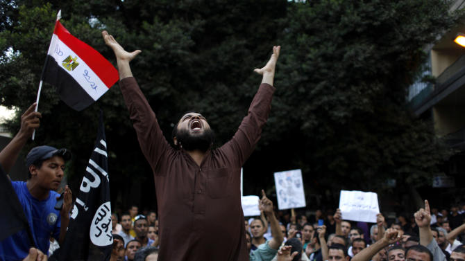 """FILE - In this Wednesday, Sept. 12, 2012 file photo, Egyptian protesters carry their national flag and a flag with Arabic that reads """"No God but Allah, and Mohammed is his prophet,"""" and chant anti U.S. slogans during a demonstration in front of the U.S. embassy in Cairo, Egypt, as part of widespread anger across the Muslim world about a film ridiculing Islam's Prophet Muhammad. U.S.-funded ads on Pakistani television include President Barack Obama extolling America's religious tolerance. To many in the Muslim world, this misses the mark in efforts to calm the outrage over a film mocking the Prophet Muhammad. (AP Photo/Nasser Nasser, File)"""