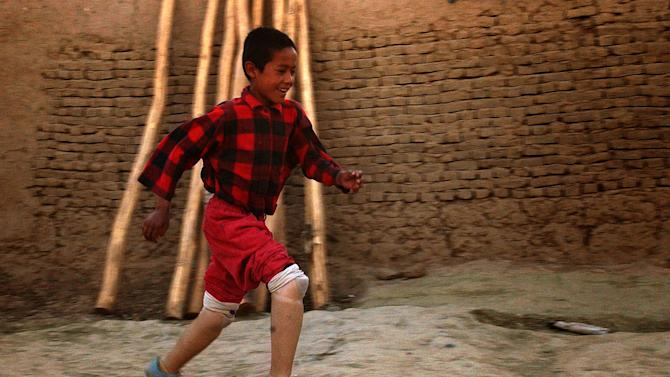 """In this June 19, 2004 photo, Mohammed, 12, runs using his new pair of prosthetic legs at his home in a Kabul suburb in Afghanistan.  In Afghanistan, Associated Press photographer Emilio Morenatti had visited a rehabilitation center run by the Red Cross in Kabul that was considered one of the best in the country and was one of the few that provided prostheses to patients, including children, who had been blown up by forgotten mines in rural areas. Morenatti's world changed on Aug. 11, 2009 when during his embed in southern Afghanistan with the U.S. military, which was to have been his last patrol before going home, the eight-wheel armored Stryker vehicle in which he was traveling with U.S soldiers hit a roadside bomb and flipped over, knocking him unconscious. """"I never stop thinking about those Afghan patients and how they were facing their rehabilitation process even in that calamitous center,"""" writes Morenatti, who lost his leg below the knee in the bomb blast. (AP Photo/Emilio Morenatti)"""