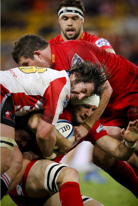 Queensland Reds player Adam Wallace-Harrison (bottom) is tackled by Golden Lions player Cobus Grobbelaar (C) during their Super 15 rugby union match at Suncorp Stadium in Brisbane on May 19, 2012.  IM