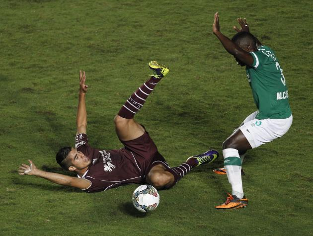 Casierra of Deportivo Cali reacts as he and Benitez of Lanus fight for the ball during Copa Libertadores match in Cali