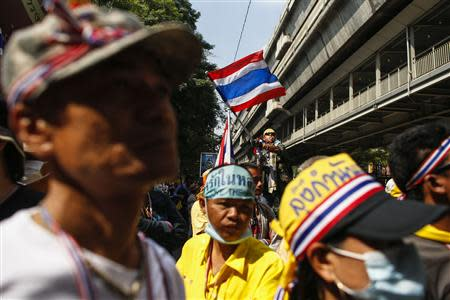 Anti-government protester waves a Thai national flag as he gathers with others during a rally at the Thai Police Headquarters in Bangkok
