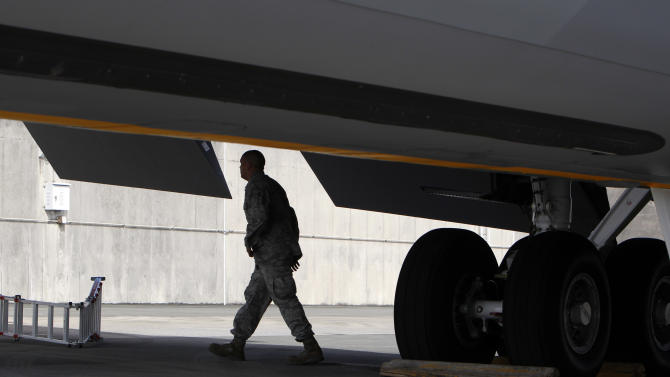 In this Aug. 14, 2012 photo, a ground crew member walks under the wing of a U.S. Air Force KC-135 Stratotanker, which was built in 1958, at Kadena Air Base on Japan's southwestern island of Okinawa.  For decades, the U.S. Air Force has grown accustomed to such superlatives as unrivaled and unbeatable. Now some of its key aircraft are being described with terms like decrepit.  (AP Photo/Greg Baker)