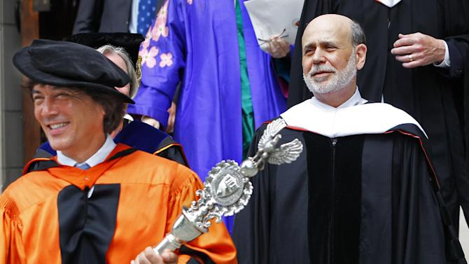Princeton University's Dr. Jeff Nunokawa, Professor of English, holds the the school's ceremonial mace as Ben S. Bernanke, Chairman of the Federal Reserve lead the processional out of Princeton University Chapel after giving the Baccalaureate address during an interfaith service in Princeton, N.J. Sunday, June 2, 2013. (AP Photo/Rich Schultz)