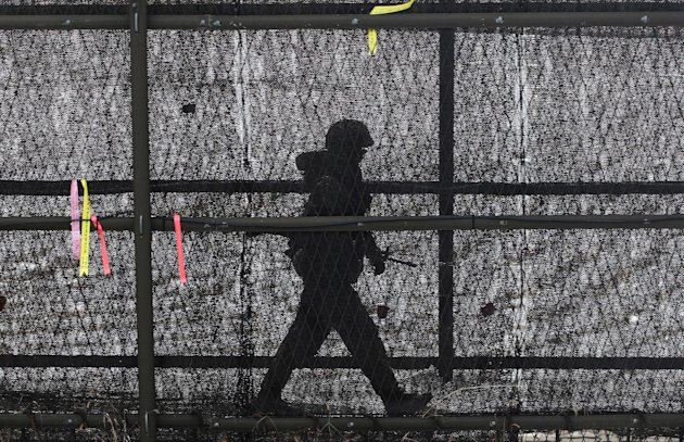 A South Korean army soldier patrols inside the barbed-wire fence at Imjingak in Paju near the demilitarized zone (DMZ) of Panmunjom, South Korea, Sunday, Feb. 17, 2013. North Korea is upgrading one of its two major missile launch sites, apparently to handle much bigger rockets, and some design features suggest it is getting help from Iran, a U.S. research institute said last Thursday. (AP Photo/Ahn Young-joon)