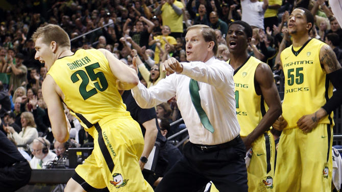 FILE - In this Jan. 26, 2013, file photo, Oregon forward E.J. Singler (25) runs downcourt past head coach Dana Altman and the bench, including guard Damyean Dotson (21) and center Tony Woods (55), after hitting a 3-pointer against Washington in an NCAA college basketball game in Eugene, Ore. In a season of parity that has produced quite a few surprises, a few of the unexpected turns, such as Oregon's success, have stood out. (AP Photo/Chris Pietsch, File)