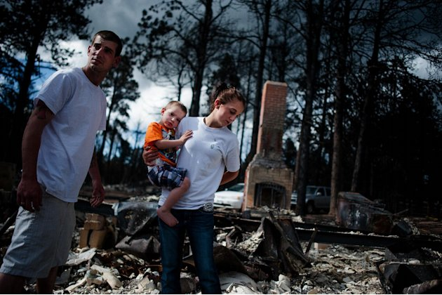 Ritchie Lewis, Brandy Burton and their son Caiyleb Lewis, 2, help sift through the rubble of their family's home that was completely destroyed in the Black Forest Fire, Tuesday, June 18, 2013, in Colo