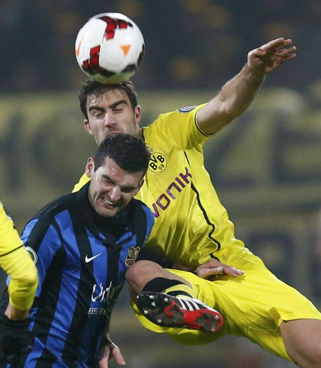 Rathgeber of Saarbruecken challenges Borussia Dortmund's Sokratis during their German soccer cup DFB Pokal third round match in Saarbruecken