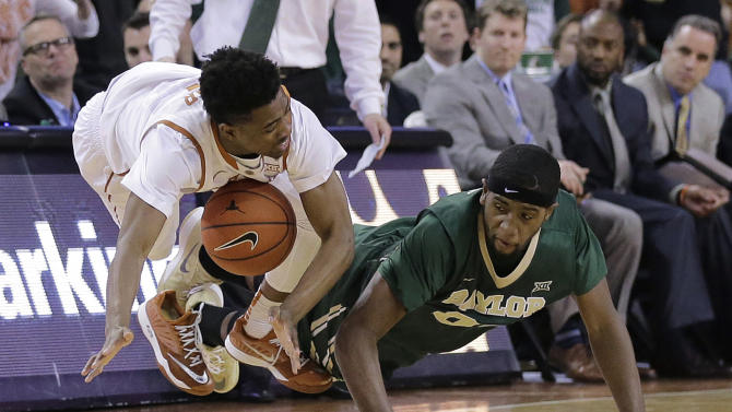 Texas' Isaiah Taylor, left, and Baylor's Royce O'Neale, right, chase a loose ball during the second half of an NCAA college basketball game, Monday, March 2, 2015, in Austin, Texas. Texas won 61-59 in overtime. (AP Photo/Eric Gay)