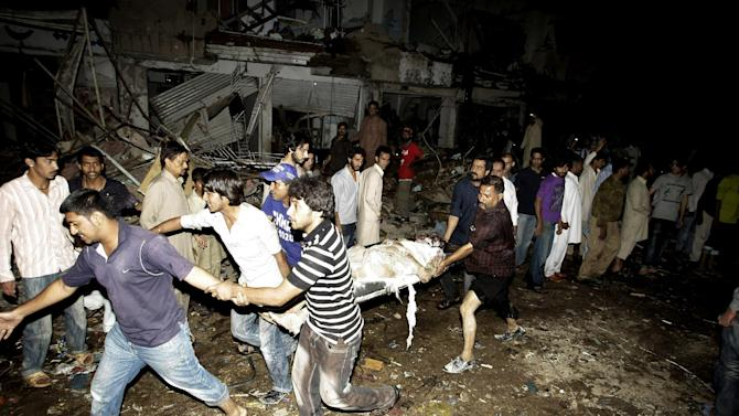 Pakistani men carry the body of a man from the site of a bomb blast in Karachi, Pakistan, Sunday, March 3, 2013. Pakistani officials say a bomb blast has killed dozens of people in a neighborhood dominated by Shiite Muslims in the southern city of Karachi. (AP Photo/Fareed Khan)
