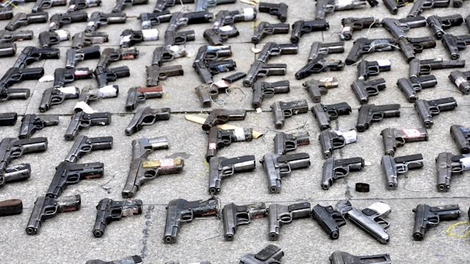 Pistols confiscated by the authorities are seen displayed on the ground during a massive destruction event of illegal weapons in Garze Tibetan Autonomous Prefecture