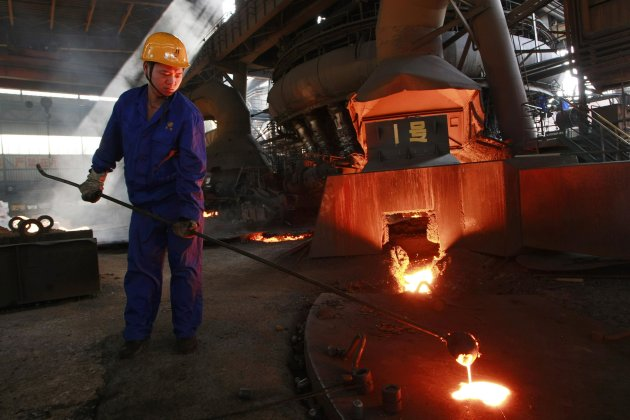 A labourer works next to a furnace at a steel factory in Hengyang