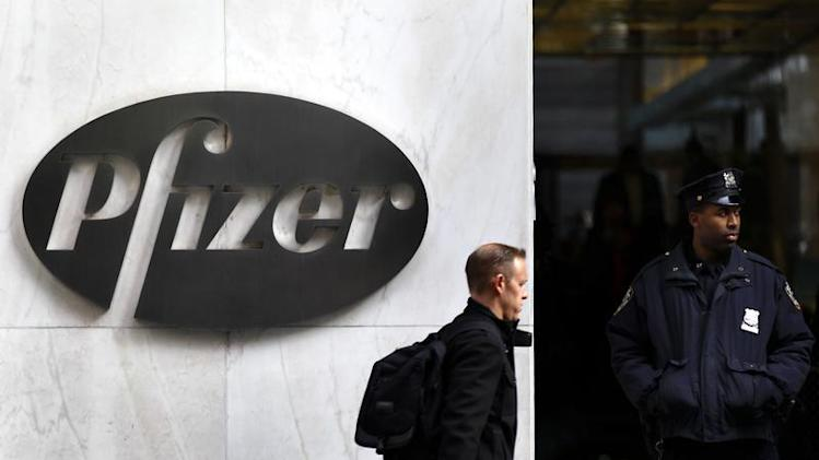 A man walks past the Pfizer logo next to a New York Police Officer standing outside Pfizer's world headquarters in New York