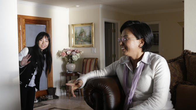 In this Monday, March 11, 2012 photo, Victoria Hu, left, waves at her mother, Hong Li at their house in Rancho Palos Verdes, Calif. Although it has often left Victoria angry, her family's ordeal has also made her decide that she should live every day of her own life to the fullest. She got accepted to the University of California, Berkeley, where she is a junior majoring in political economy. Because of her father's ordeal, she wants to learn more about the law. When not studying, she's taken up drama, horseback riding and martial arts. She works part-time for a small Internet start-up that produces online comics, and she recently tried skydiving. (AP Photo/Chris Carlson)