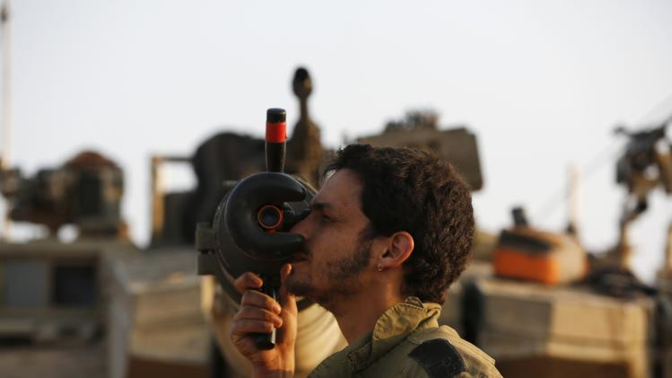 An Israeli soldier adjusts sights on a tank outside the northern Gaza Strip
