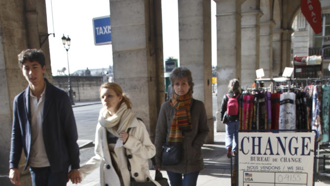 People walk past exchange rate boards in Paris, Friday, March 6, 2015. The euro could soon be doing something it's only done a couple of times in its 16-year existence, trading 1-to-1 with the dollar. Europe's single currency has since May been on a downward trajectory again the dollar, mainly because of the divergence in economic performance between the eurozone an the United States. (AP Photo/Michel Euler)