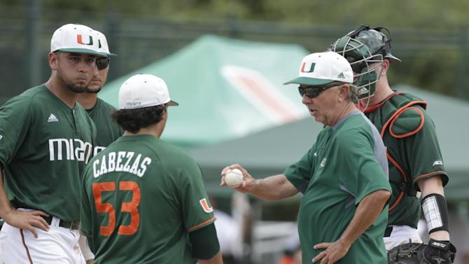 Miami head coach Jim Morris, right, gives the ball to pitcher Andrew Cabezas (53) as he replaces Danny Garcia in the sixth inning of NCAA college baseball tournament super regional game against Boston College, Saturday, June 11, 2016, in Coral Gables, Fla. (AP Photo/Wilfredo Lee)