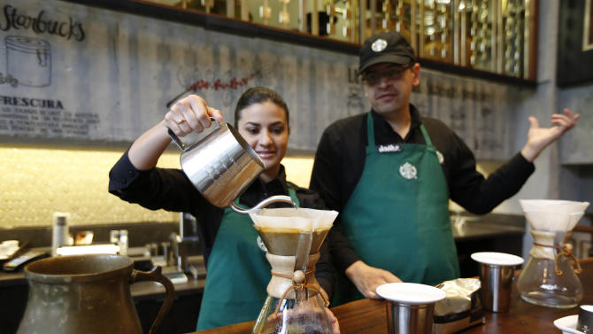 A Starbucks employee demonstrates the preparation of a cup of coffee during a media tour of the new shop in Bogota, Colombia, Wednesday, July 16, 2014. The three-floor coffee house in Bogota is the first of 50 that the Seattle-based company plans to open here in the next five years. (AP Photo/Fernando Vergara)