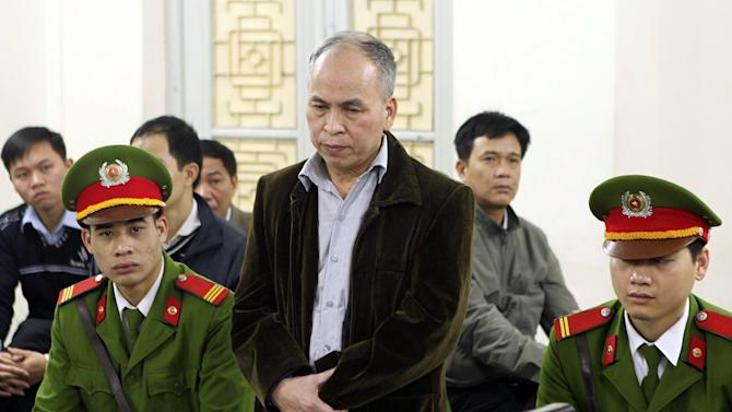 """Dissident blogger Pham Viet Dao, standing at center, appears at a court in Hanoi, Vietnam Wednesday March 19, 2014. Vietnamese court on Wednesday sentenced the dissident blogger to 15 months in prison for posting online criticism of the government, the latest case in an intensifying crackdown against dissent in the one-party communist country. Dao was found guilty of """"abusing democratic freedoms to infringe the interests of the state"""" by posting dozens of articles that """"distorted, vilified and smeared the senior leaders"""" and sentenced to 15 months in prison in the trial that lasted two hours. (AP Photo/Vietnam News Agency, Doan Tan)"""