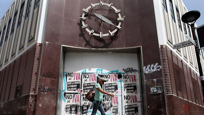 "A woman walks in front of a closed down bank in the neighborhood of Rio Piedras in San Juan, Puerto Rico, Monday, June 29, 2015. The bills on the closed bank doors read in Spanish ""No to the value added tax. Let the rich pay for the crisis."" International economists released a critical report on Puerto Rico's economy Monday on the heels of the governor's warning that the island can't pay its $72 billion public debt. (AP Photo/Ricardo Arduengo)"