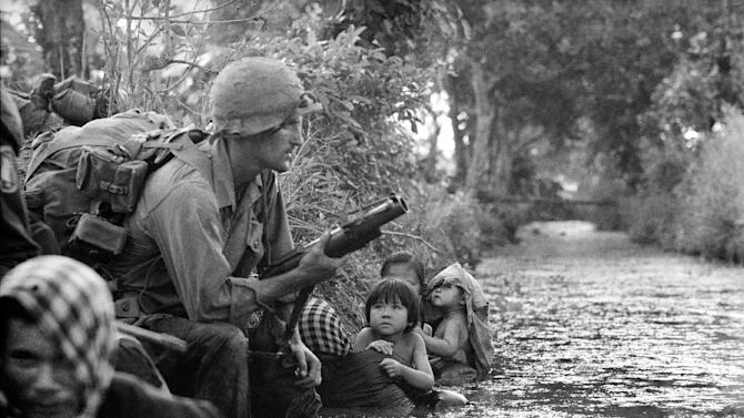 FILE - In this Jan. 1, 1966 file photo, two South Vietnamese children gaze at an American paratrooper holding an M79 grenade launcher as they cling to their mothers who huddle against a canal bank for protection from Viet Cong sniper fire in the Bao Trai area, 20 miles west of Saigon, Vietnam. Faas, a prize-winning combat photographer who carved out new standards for covering war with a camera and became one of the world's legendary photojournalists in nearly half a century with The Associated Press, died Thursday May 10, 2012. He was 79. (AP Photo/Horst Faas)