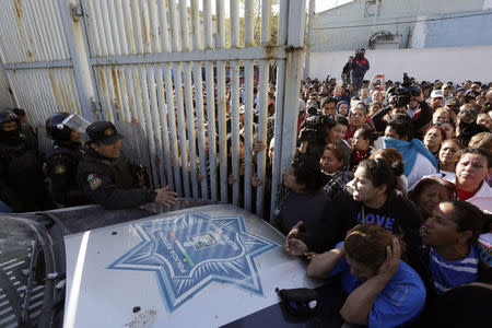 Family members of inmates argue with police at the entrance of the Topo Chico prison in Monterrey