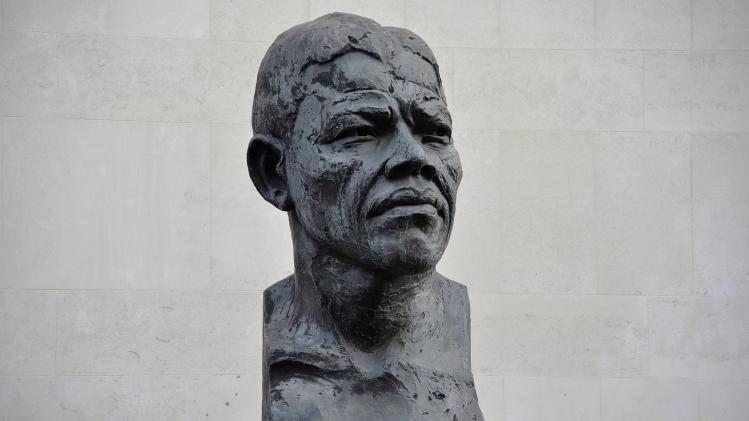 A flower is seen placed on a statue of former South African President Nelson Mandela on the South Bank in central London