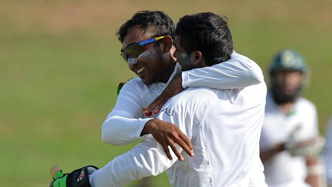 Sri Lanka's Mahela Jayawardene (L) and wicketkeeper Niroshan Dickwella celebrate the dismissal of South Africa's Faf du Plessis during the second day of the second Test in Colombo on July 25, 2014
