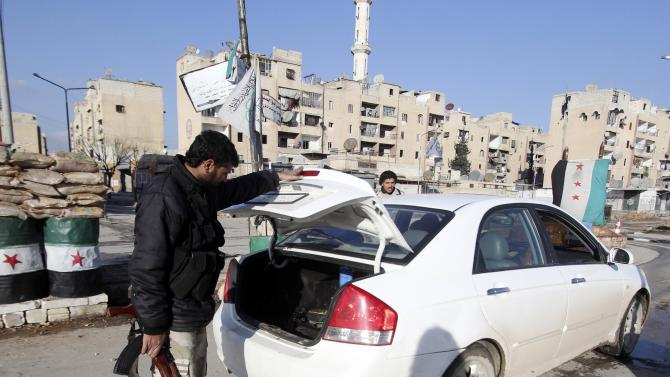 Rebel fighters of the al-Jabha al-Shamiya check a car's boot at a checkpoint in the Masaken Hanano neighbourhood of Aleppo