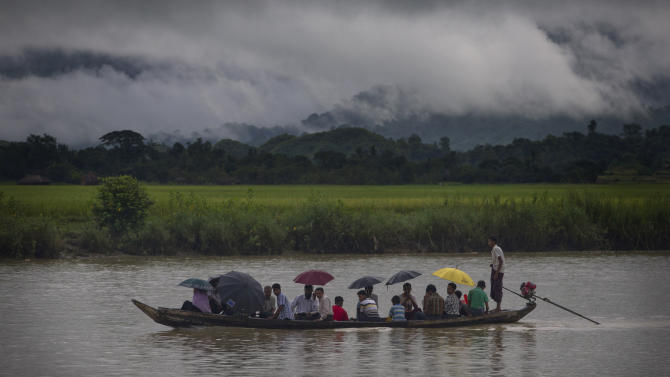 In this Sept. 16, 2013 photo, villagers travel in a river close to Buthidaung in Rakhine state, Myanmar. After closing its doors to the West for half a century, Myanmar has reopened, inviting all to come and discover its treasures, ancient palaces of kings long gone, legends and mysteries told in stone. With ill-equipped roads and railways, there is no better way to explore than by river. Public ferries crisscross through glistening green paddies; old teak fishing boats can be rented by the day. (AP Photo/Gemunu Amarasinghe)