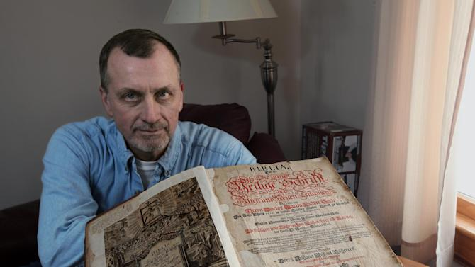 Tim Shier holds up his family bible dating from the 1700's on Feb. 3, 2013 in his home in Marysville, Ohio. The Lutheran Bible, written in German Gothic script and containing the handwritten dates of births, deaths and marriages for seven generations of Tim Shier's family, went missing in the burglary in Marysville, near Columbus, in December 2011. But thanks to a bit of luck, a sharp-eyed family member, local deputies and Goodwill, which had ended up with the Bible and then sold it online, the heirloom is back in Shier's hands. (AP Photo/The Columbus Dispatch, Chris Russell)