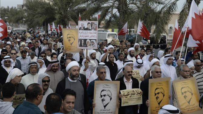 Protesters holding pictures of Al Waad President Ebrahim Shareef march during an anti-government rally organised by Bahrain's main opposition party, Al Wefaq in Budaiya west of Manama