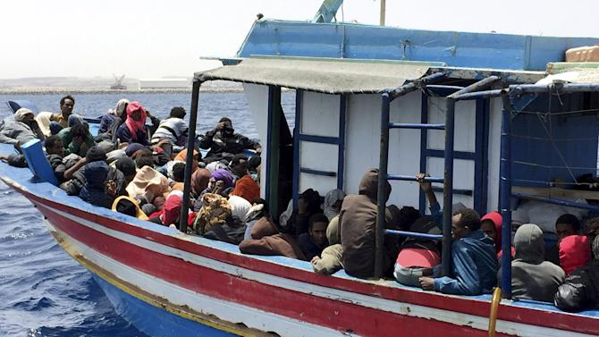 Illegal migrants who attempted to sail to Europe, sit in a boat carrying them back to Libya, after their boat was intercepted at sea by the Libyan coast guard, at Khoms, Libya