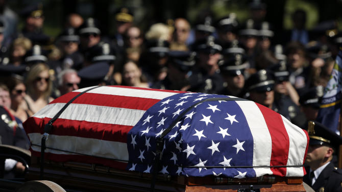 The casket of fallen Indianapolis police Officer Perry Renn is draped with an American flag during a funeral service Friday, July 11, 2014, in Indianapolis. Renn died Saturday night after being shot three times by a man armed with an AK-47 assault rifle. (AP Photo/Darron Cummings)