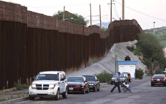 In this Aug. 9, 2012, photo, vehicles are parked along the border fence as pedestrians cross the street in Nogales, Mexico. The location is near the site where a U.S. Border Patrol agent being pelted with rocks opened fire toward Mexico, killing a 16-year-old boy. The shooting has prompted renewed outcry over the Border Patrol's use-of-force policies and angered human rights activists and Mexican officials who believe the incident has become part of a disturbing trend along the border _ gunning down rock-throwers rather than using non-lethal weapons. (AP Photo/Ross D. Franklin)