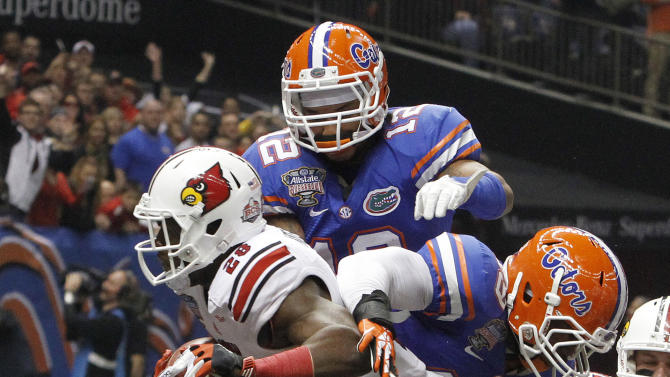 Louisville running back Jeremy Wright (28) scores a first quarter touchdown as Florida linebacker Darrin Kitchens (49) and linebacker Antonio Morrison (12) defend in the Sugar Bowl NCAA college football game Wednesday, Jan. 2, 2013, in New Orleans. (AP Photo/Butch Dill)