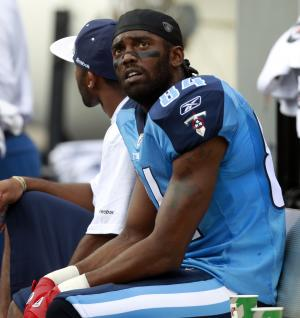 In this file photo taken Nov. 14, 2010, Tennessee Titans' Randy Moss sits on the bench during an NFL football game against the Miami Dolphins in Miami. New Orleans Saints general manager Mickey Loomis said the club has held a workout with the veteran receiver, who is trying to make a comeback after spending a year out of football. (AP Photo/Alan Diaz, file)