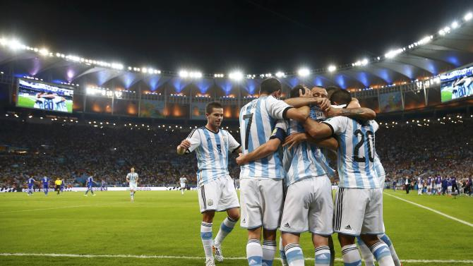 Argentina's Messi is congratulated by his teammates after scoring a goal against Bosnia during their 2014 World Cup Group F soccer match at the Maracana stadium in Rio de Janeiro