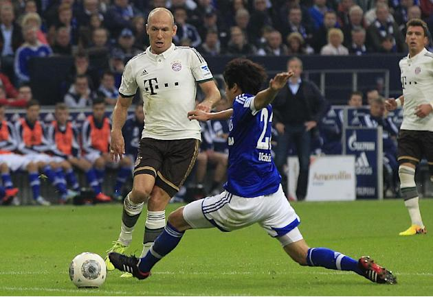 Bayern's Arjen Robben of the Netherlands, left, and Schalke's Atsuto Uchida of Japan challenge for the ball during the German first division Bundesliga soccer match between Schalke 04 and Bayern Munic