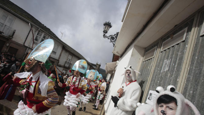 "Carnival revellers dressed as ""Peliqueiros"" run along a street in Spain's northwestern village of Laza"