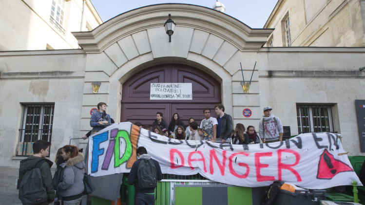 """Students set up barricades and display a banner reading """"Education in danger"""" outside their highschool to protest against immigration policy, in Paris, Thursday, Oct.17, 2013. Kosovan girl Leonarda Dibrani was finishing up a field trip when French police showed up at the bus, detaining the 15-year-old schoolgirl in front of her classmates before authorities expelled her to Kosovo because her family's asylum application had been rejected. The incident earlier this month, but which was made public this week, has sparked outrage from immigrant groups and others who say police went too far in publicly shaming the teenager. (AP Photo/Jacques Brinon)"""