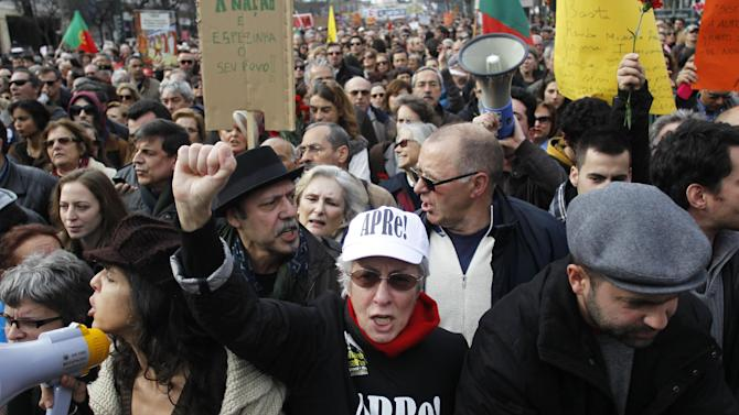 "In this photo taken on March 2, 2013, Portuguese retired woman Maria Luisa Cabral, center, shouts slogans during a protest against austerity measures taking by the Portuguese government, in Lisbon. . Taxes and cuts in previous years had already cut pensioners income by 20 percent as the government looked to cut the national debt. Words in Cabral's t-shirt read in Portuguese: ""APRE! We are not disposables!"". APRE is a Portuguese retired people association. (AP Photo/Francisco Seco)"