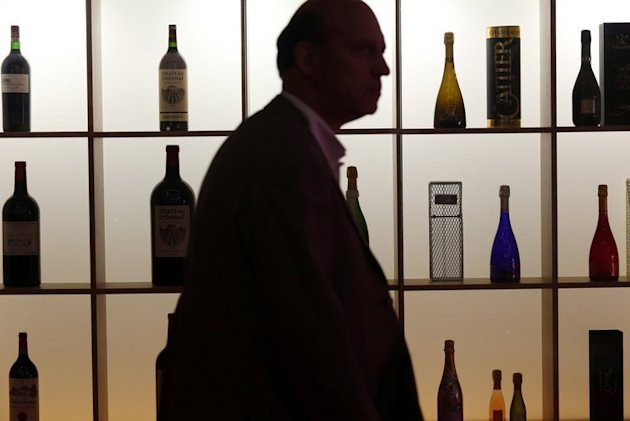 A man walks past a wall of wine bottles at the Vinexpo trade fair in Bordeaux, southwestern France, on June 17, 2013