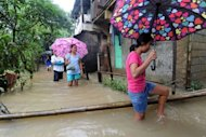 People wade through floodwaters in Quezon City Suburban Manila on August 6, 2012. Residents of low-lying slums fled the huge shantytowns lining Manila&#39;s rivers and sewers for the safety of schools, gymnasiums and government buildings, the civil defence office said